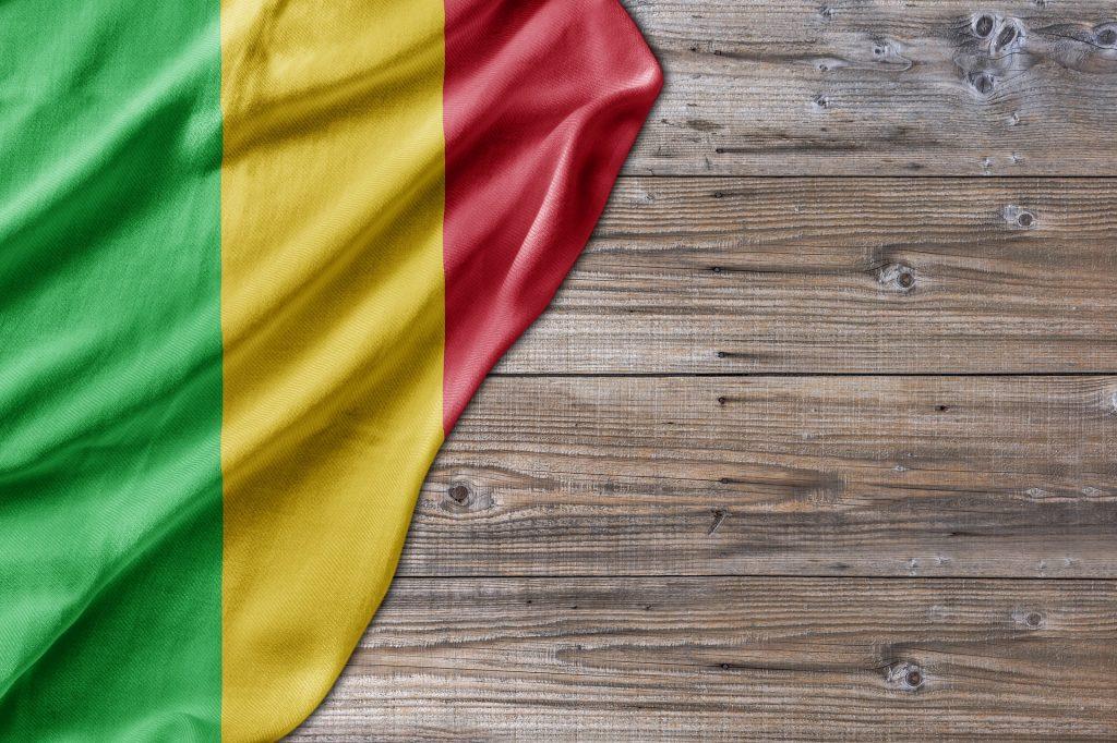 Imagem de um tecido com as cores do reggae:  verde, amarelo e vermelho, representando a bandeira so estilo. Está disposta sobre uma mesa de madeira.