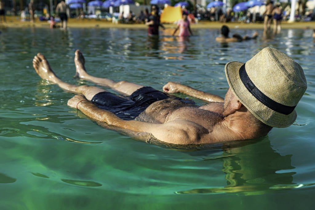 Homem flutuando em um lago. Ele usa uma bermuda azul e  um chapéu de palha com uma fita preta. No lago também se encontram outras pessoas.