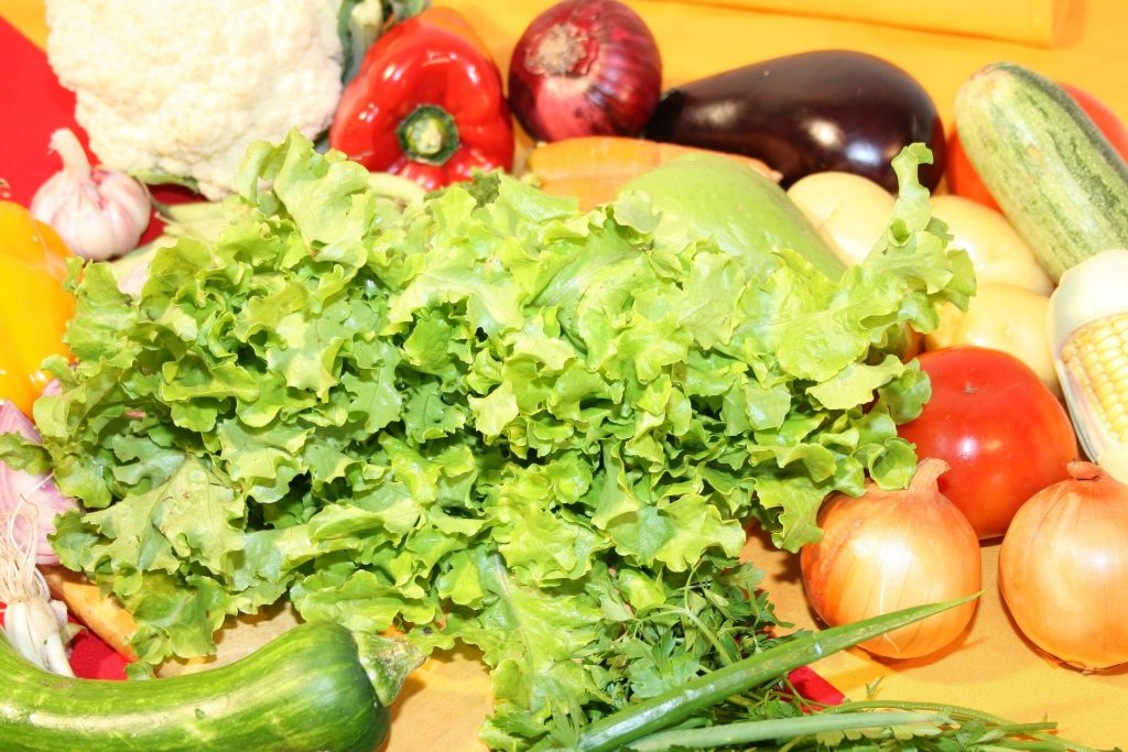 Imagem de uma bancada cheia de alimentos saudáveis como: verduras e legumes como: abobrinhas, cheiro verde, alho, couve flor, pimentão, cebola, tomate, batata, milho e cenoura.