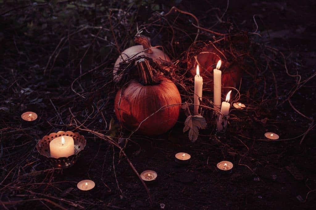 Abóbora no chão com algumas velas acesas em volta.