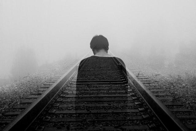 Imagem de pessoa de costas desaparecendo em trilho do trem