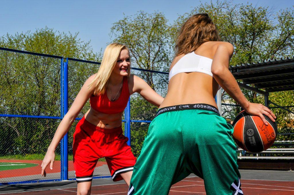 Duas mulheres vestidas com bermudas nas cores vermelha e verde e tops nas cores branco e vermelho, praticando o jogo de basquetebol.
