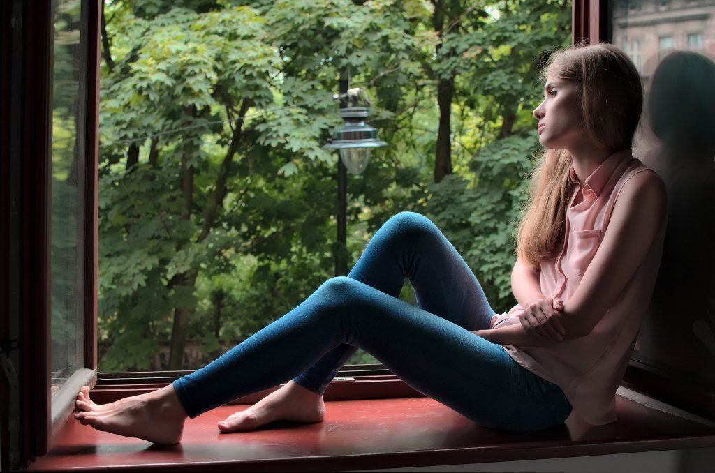 Imagem de uma menina adolescente sentada próxima a uma janela bem grande e ao fundo um lindo jardim. A garota está pensativa.