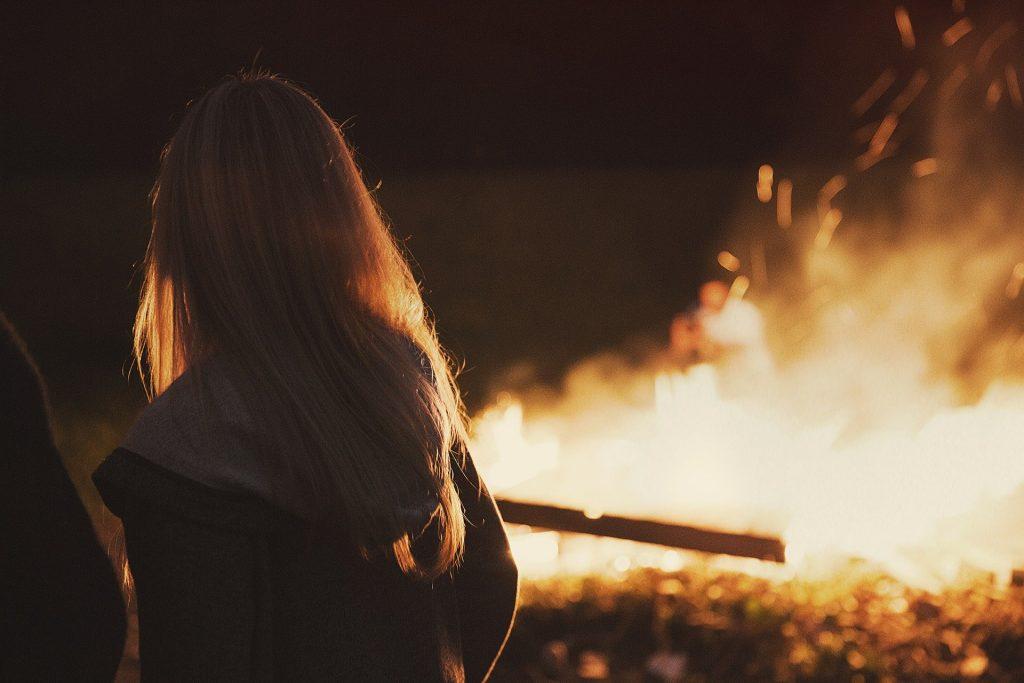 Imagem de uma mulher loura vestindo uma blusa de frio com touca. Ela está olhando para o fogo.