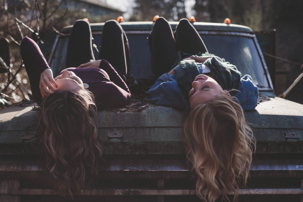 Imagem de duas garotas de cabelos longos, deitadas sobre a caçamba de uma caminhonete antiga. Elas estão felizes.