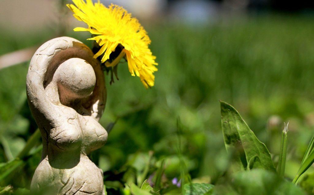 Estátua de argila branca da silhueta do corpo de uma mulher. Atrás dela há um dente de leão amarelo.