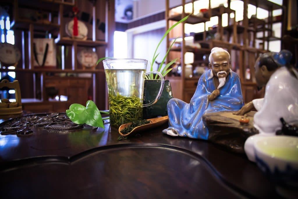 Imagem da cerimônia do chá verde. Ao fundo uma jarra de vidro com chá verde. Decoram a mesa duas estátuas de porcelana de monges budistas. É um espaço agradável e tranquilo.