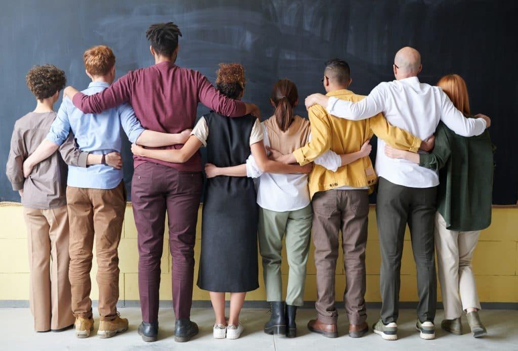 Grupo de pessoas de sexo, etnia, cor e idade diferentes, de costas, abraçados.
