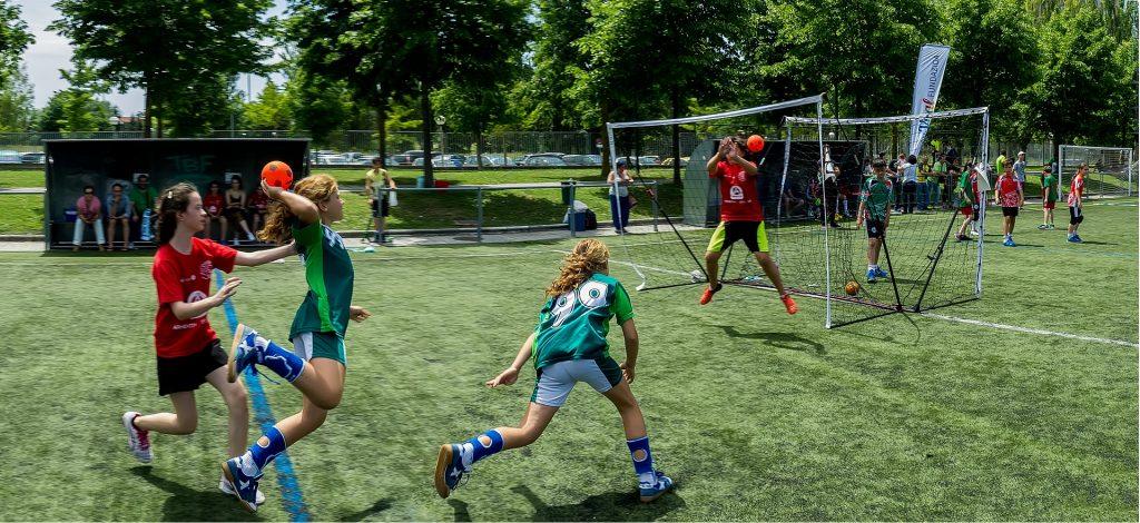 Mulheres em um campo de gramado. Elas estão treinando gols para a prática do jogo de handball.