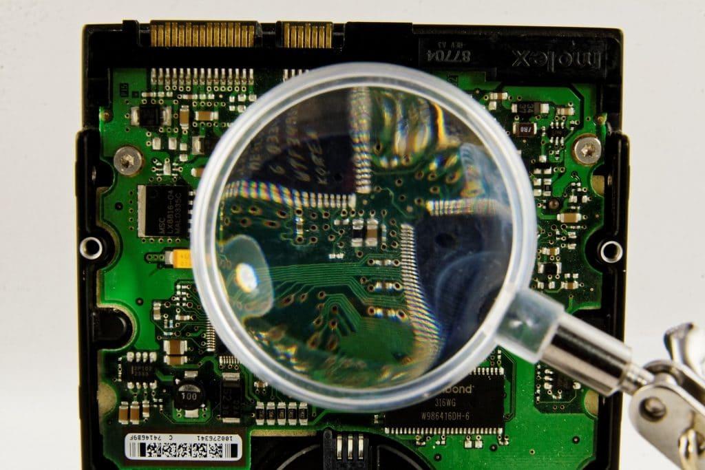 Imagem de uma unidade de disco rígido em sobre ela uma lupa.