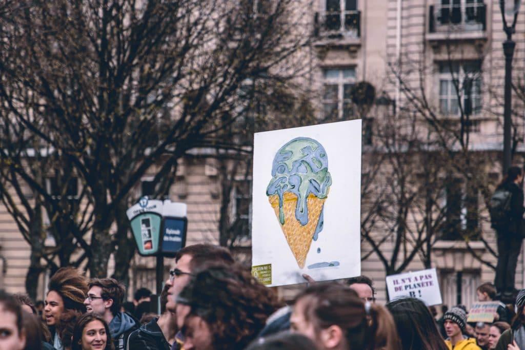 Cartaz levantado em um protesto de rua, representando o planeta Terra como uma casquinha de sorvete derretendo.