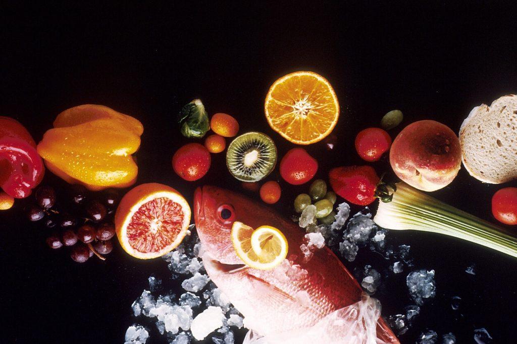 Imagem composta por vários alimentos saudáveis como: salmão, uvas, laranja, kiwi, limão, pêssego alho poró.