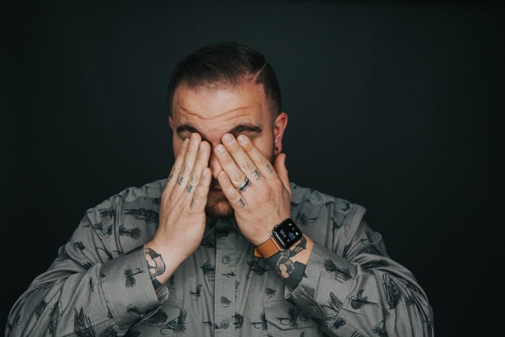 Homem usando camisa de botões e um relógio esfrega os olhos com as mãos.