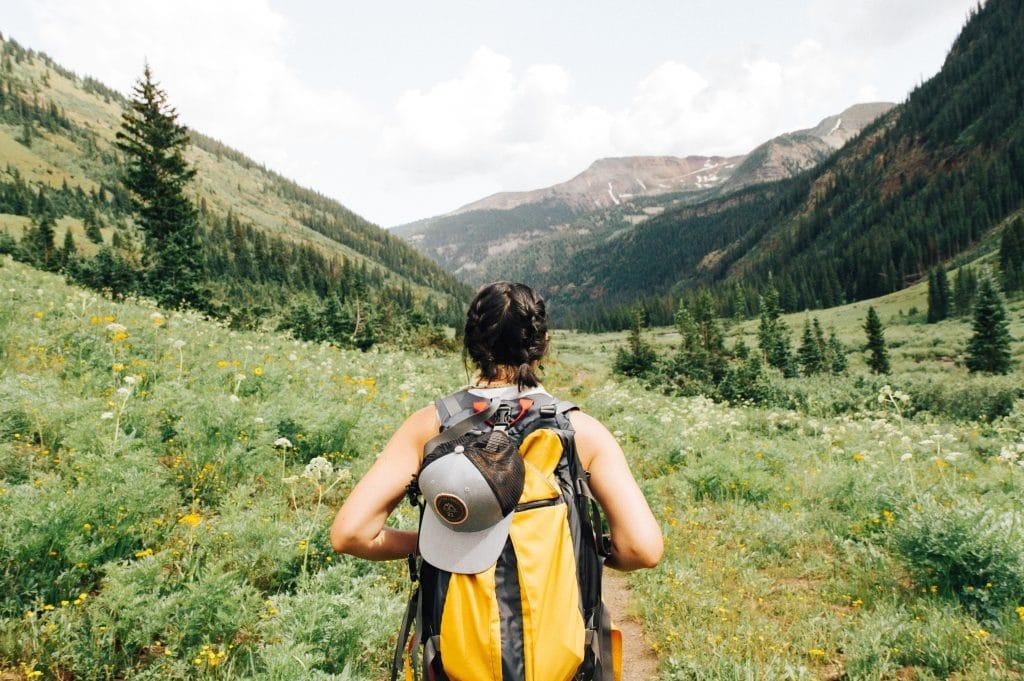 Mulher com uma mochila nas costas caminhando em um parque, cercado por flores e montanhas.