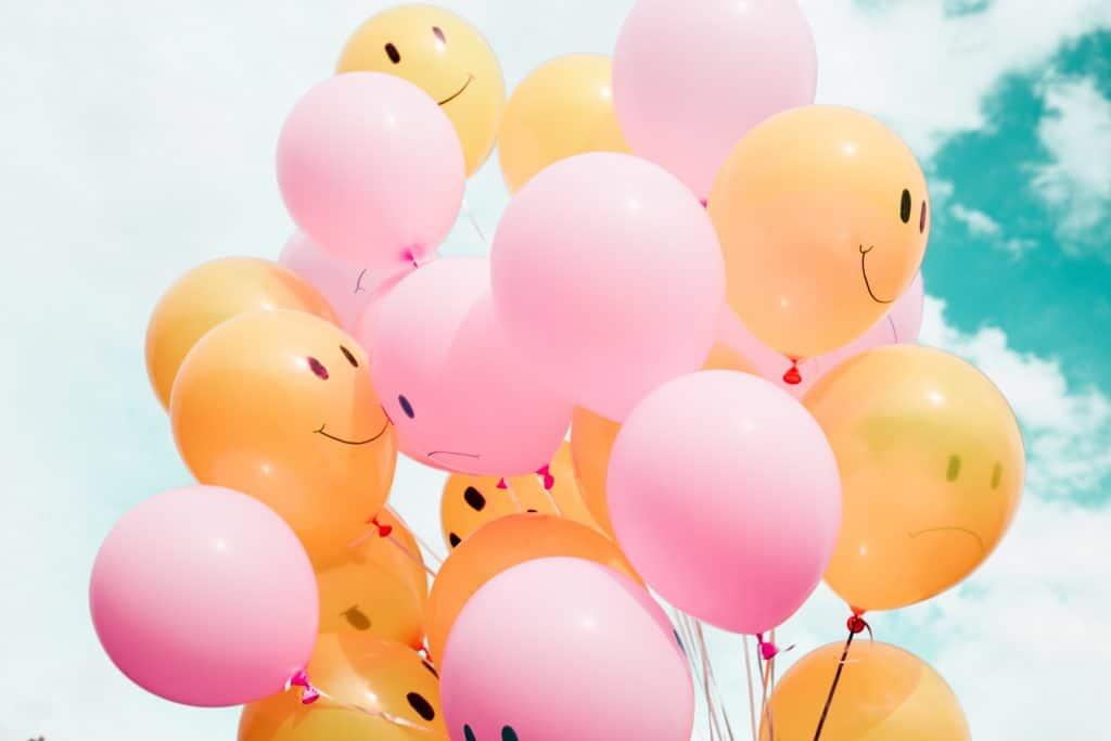 Balões de aniversário com carinhas sorridentes estampadas levantados ao céu, em um dia ensolarado.
