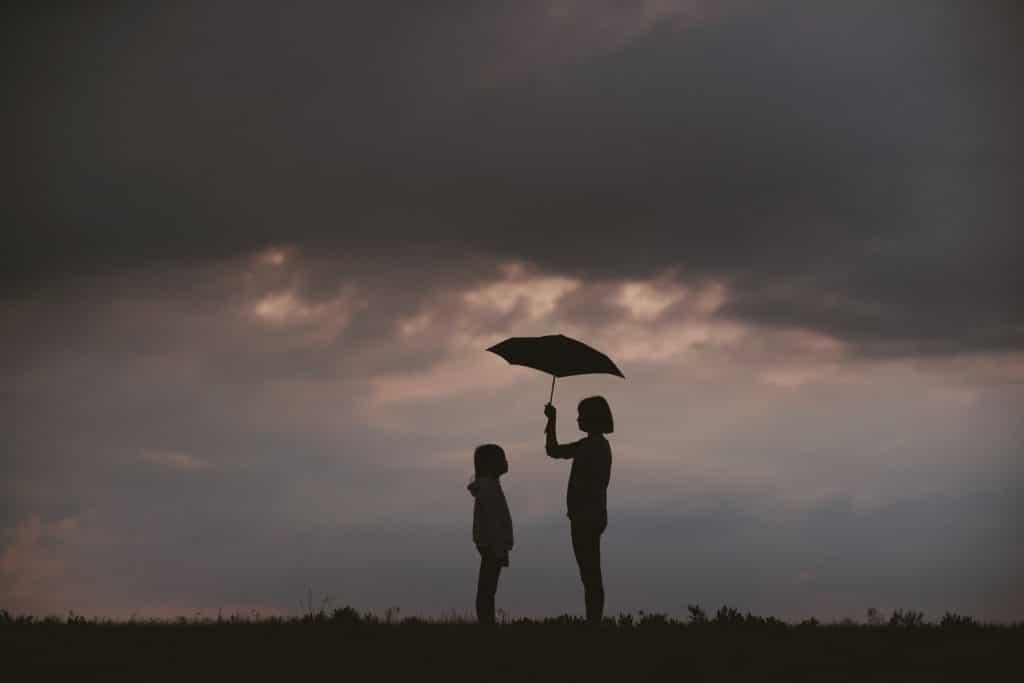 Silhueta de duas crianças em pé em um dia nublado, enquanto uma protege a outra com seu guarda-chuva.