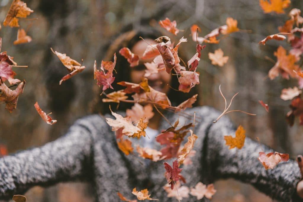 Mulher em um parque jogando folhas de outono para cima, enquanto sorri.