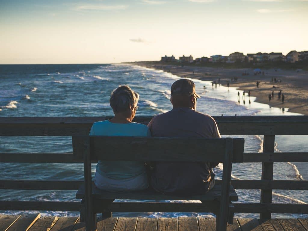 Homem e mulher idosos sentados em um banco, de frente para o mar.