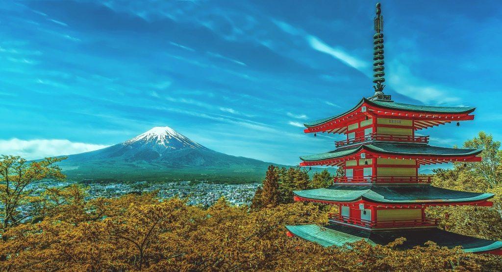 Imagem de um lindo tempo japonês nas cores branco e vermelho. Ao fundo o monte fuji coberto com a neve.