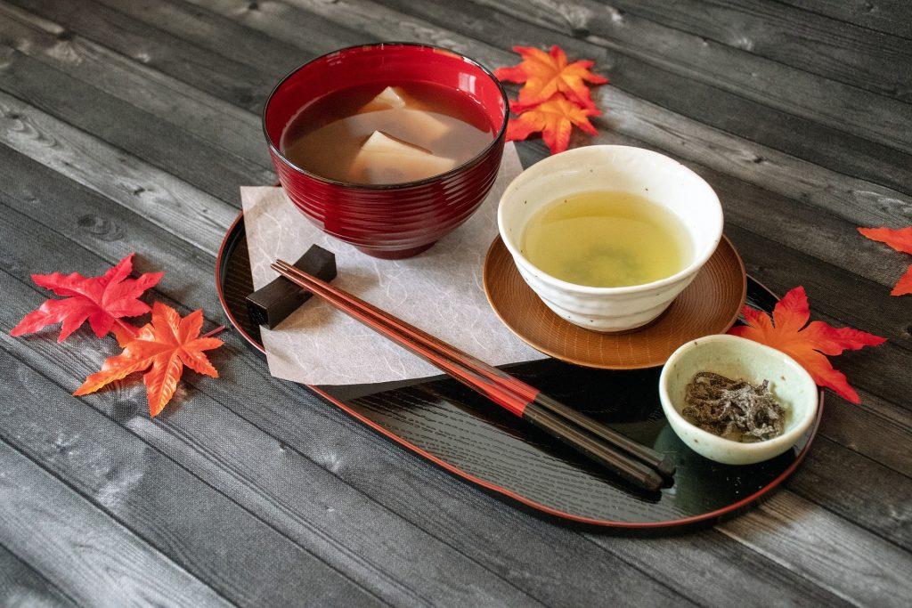 Mesa posta com vários itens para a reallização da cerimônia do chá japonesa. Os itens estão sobre uma mesa de madeira cinza decorado com folhas de outono na cor vermelha.