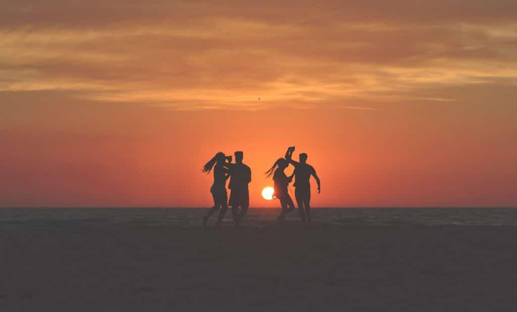 Silhuetas de dois casais dançando entre si, em uma paisagem natural, ao pôr do sol.