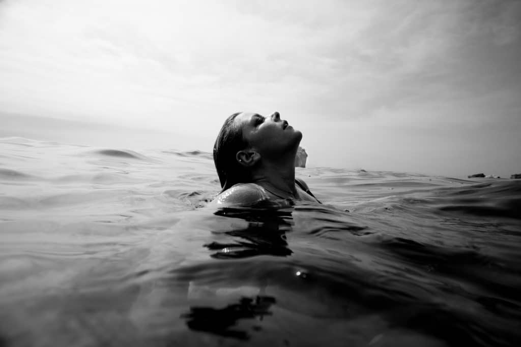 Mulher nadando no mar com a cabeça para fora como se estivesse pegando fôlego.