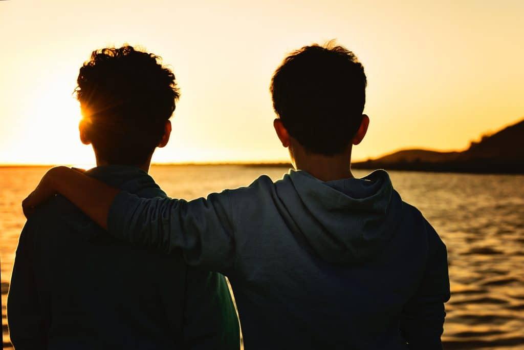 Silhueta de dois meninos de costas, abraçados, sob o pôr do sol.