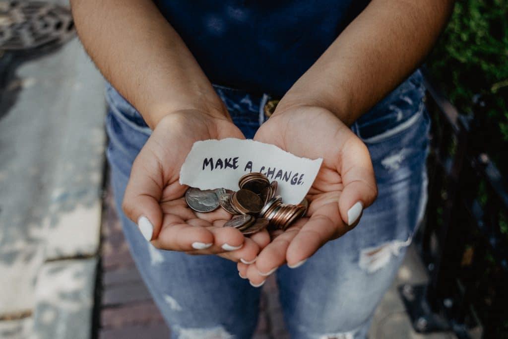 """Pessoa segurando algumas moedas com um bilhete escrito em inglês """" faça a diferença"""""""