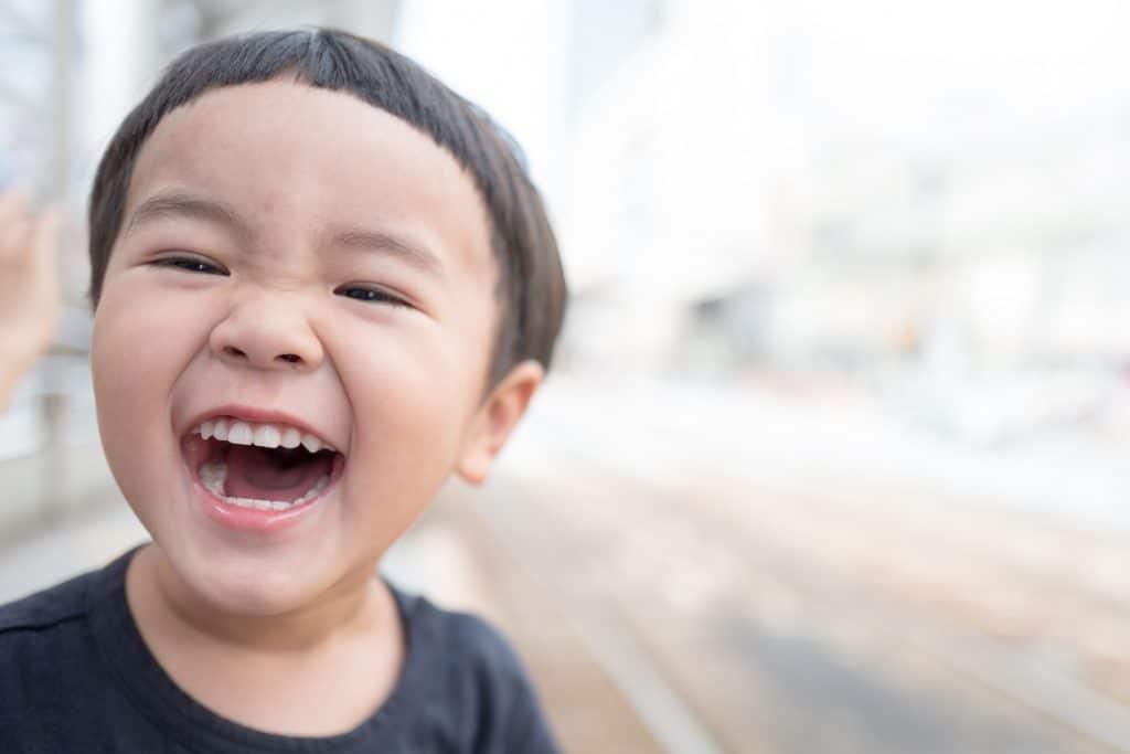 Criança sorrindo na rua durante o dia.
