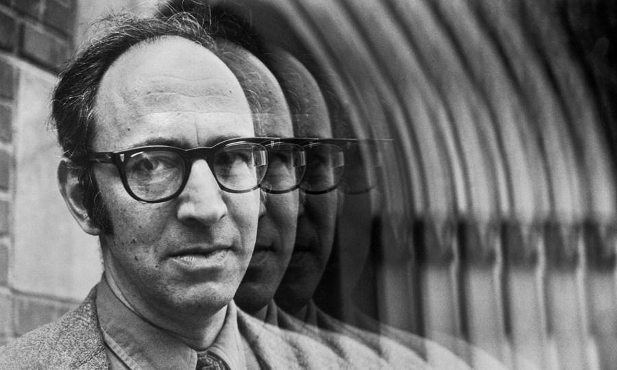 Fotografia do filósofo e cientista Thomas Khun, de óculos e roupas sociais, olhando para a câmera com expressão séria.