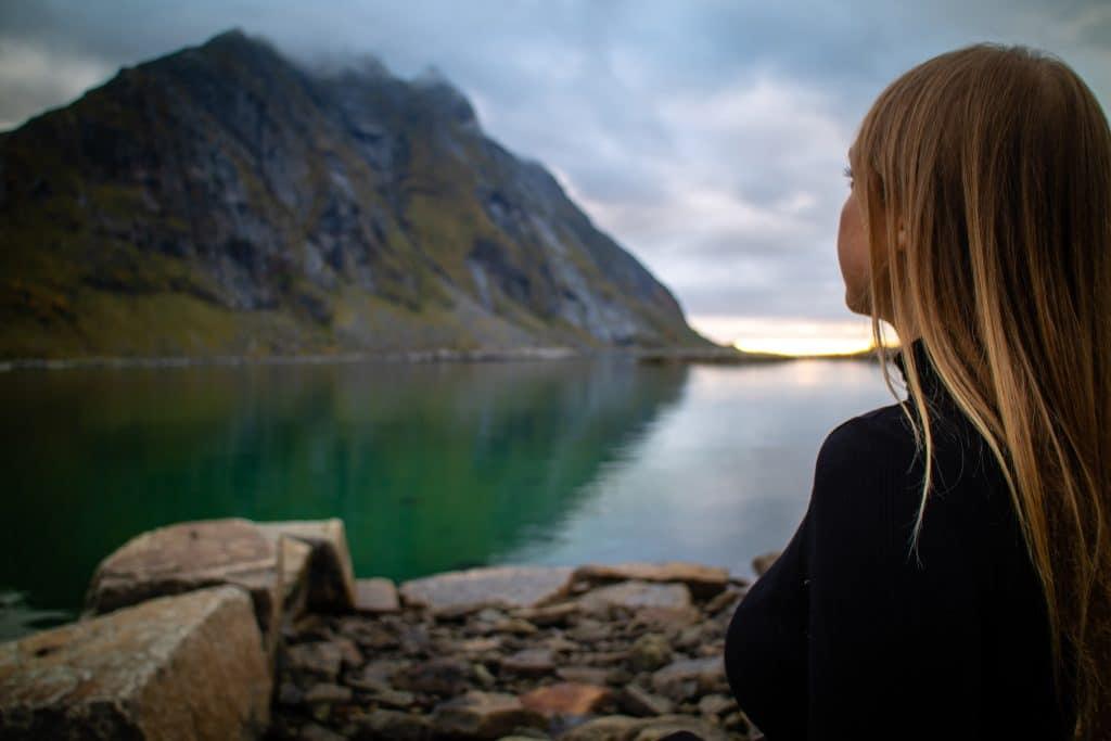Menina olhando para uma montanha em um lago.