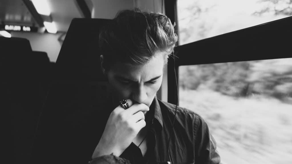 Homem pensativo sentado em um ônibus ao lado da janela