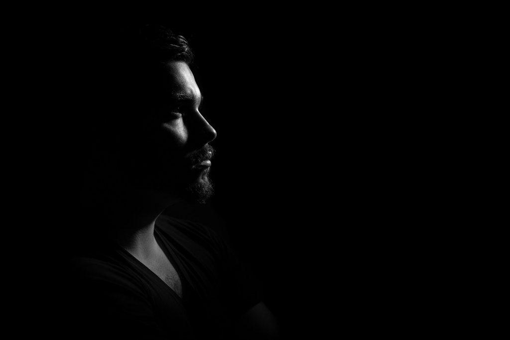 Imagem do rosto de um homem. O fundo da imagem é preto. Ele usa uma camiseta preta.
