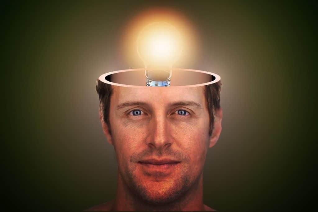 Imagem do rosto de um homem e sobre a cabeça onde fica o cérebro tem uma lâmpada acesa, iluminando as ideias do homem.