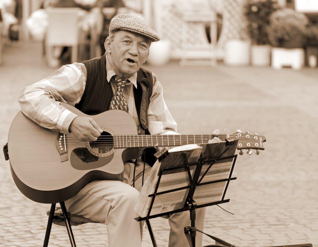 Imagem em preto e branco e um senhor usando boina e colete, sentando em uma praça. Ele está cantando e tocando um violão.