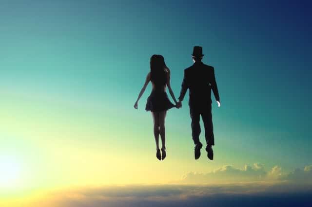 Casal de mãos dadas de costas flutuando e céul com sol ao fundo
