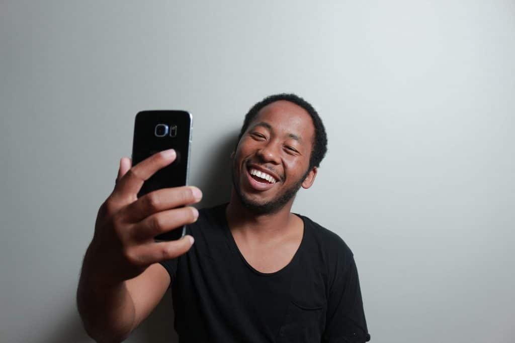 Homem tirando selfie sorrindo em parede branca