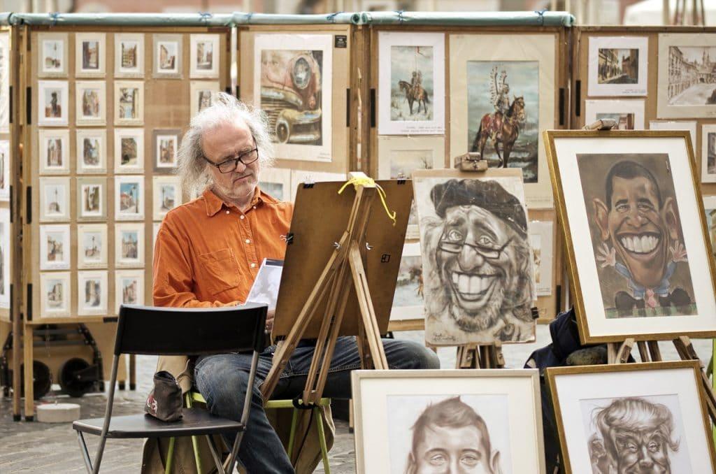 Homem idoso pintando um quadro em uma feira, com diversas exposições de desenhos e pinturas.