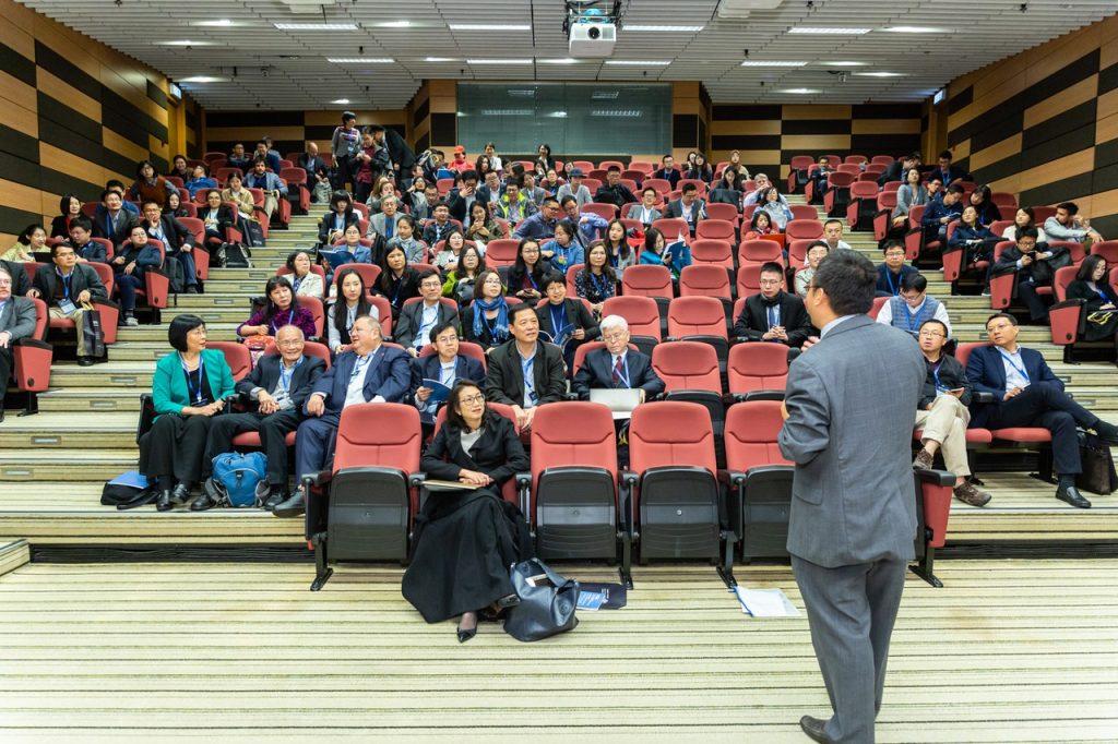 Plateia em auditório assistindo palestra, de homem que fala de costas para a câmera.