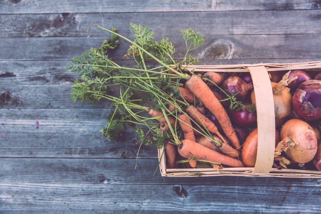 Mesa com uma cesta com cenouras e cebolas