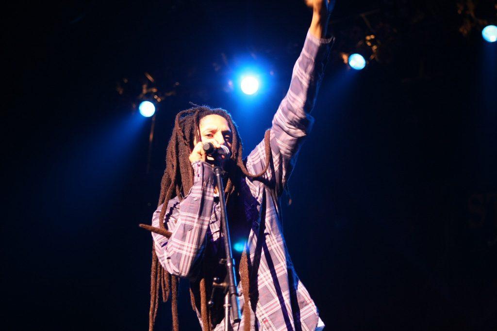 Imagem do cantor Bob Marley, ícone do reggae fazendo uma apresentação de suas músicas.