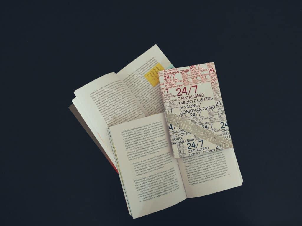 Dois livros abertos e um livro fechado dispostos um sobre o outro.