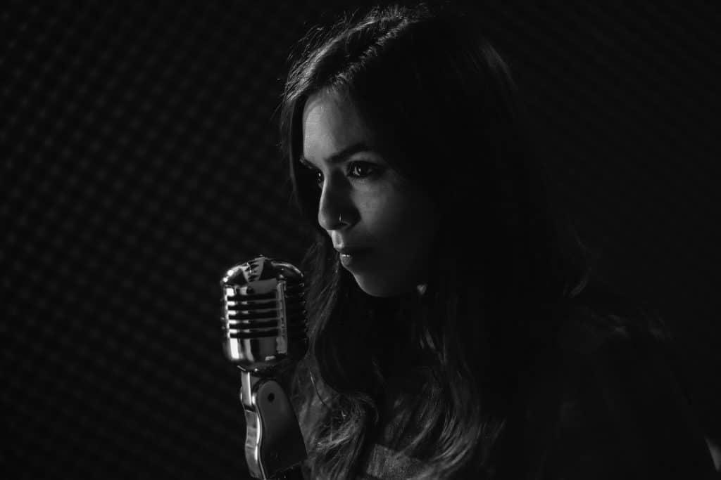 Imagem em preto e branco de uma mulher com cabelos longos. Ela está em um estúdio de gravação segurando um microfone.