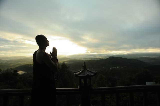 Monge em templo olhando pôr-do-sol e céu nublado