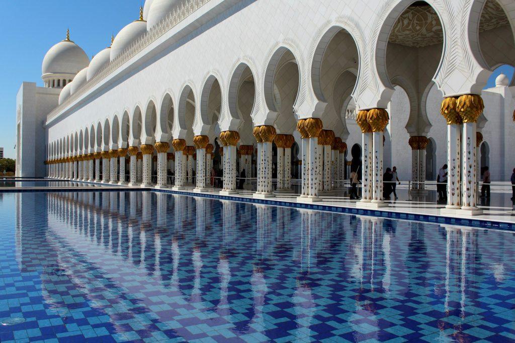 Linda mesquita pintada na cor branca e dourada. Ele é bem extensa e tem o seu reflexo em uma enorme e bonita piscina de cor azul.