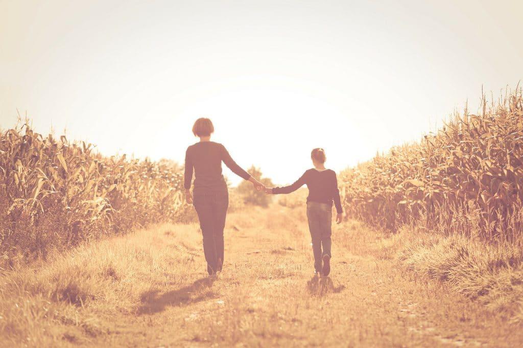 Imagem de uma mãe e sua filha. A mãe segura a mão da filha e ambas caminham por um campo de plantação de milho.