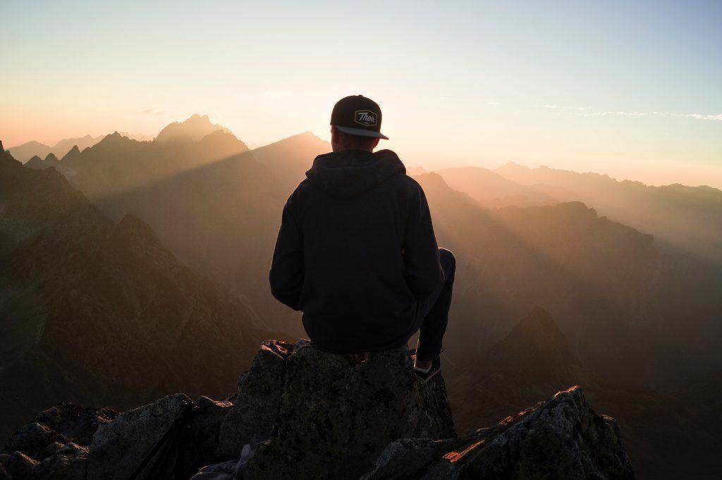 Garoto de costas sentado em montanha de costas com sol refletindo