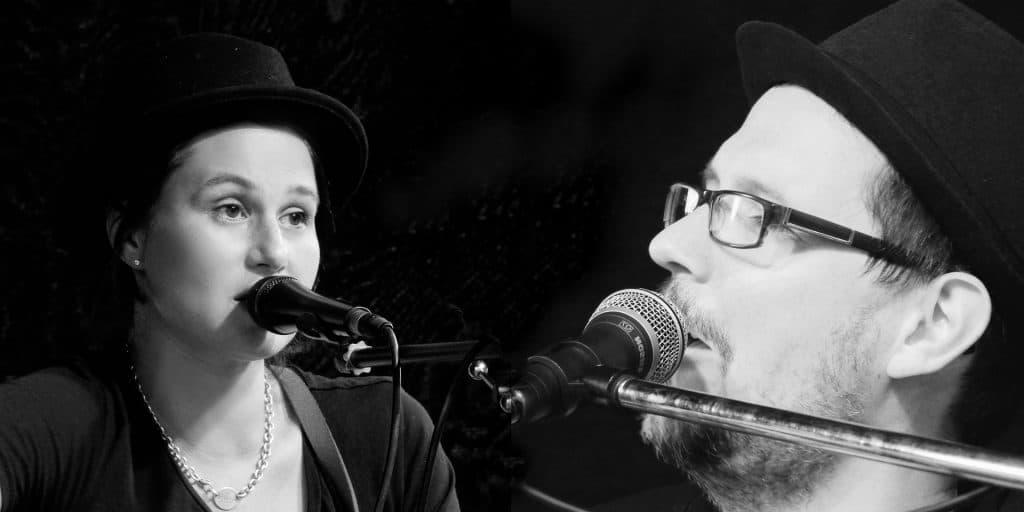 Imagem em preto e branco de um casal hetero. Ambos estão sentados, usam um chapéu preto e estão cantando uma música com microfones próximos às suas bocas.