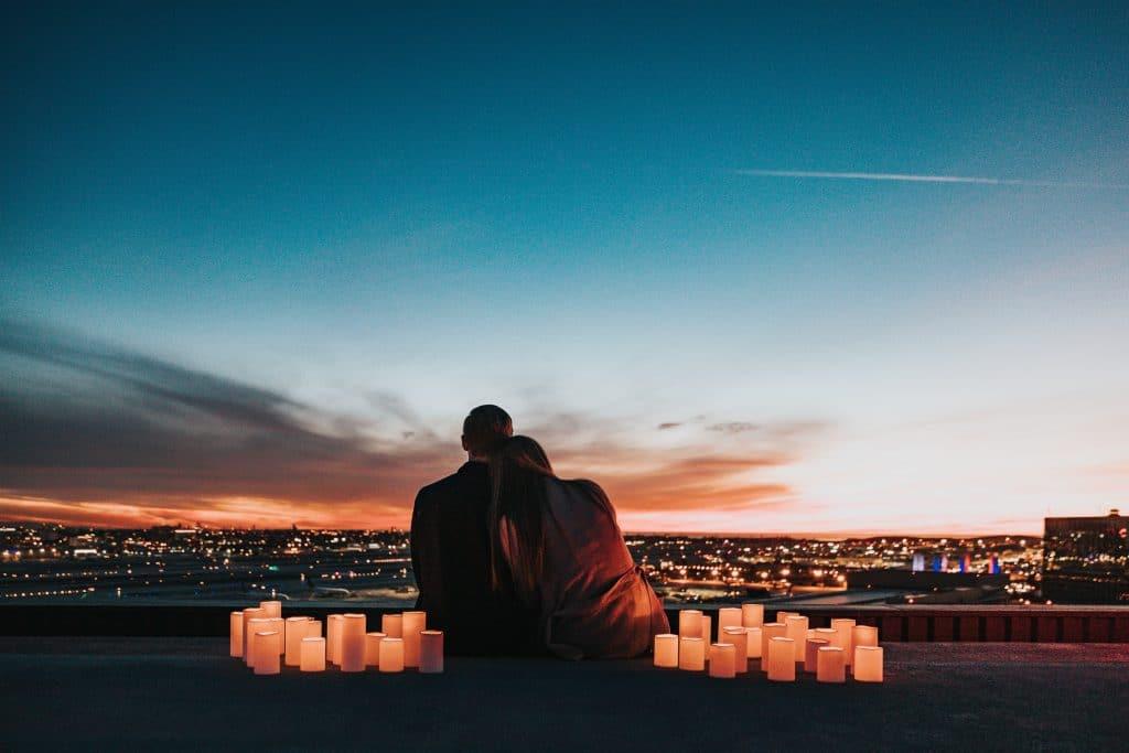 Casal sentado no topo de um prédio, rodeado por velas acesas, ao pôr do sol.
