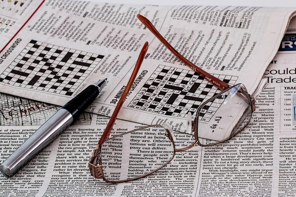 Imagem de um jornal com vários jogos de palavras cruzadas. Sobre o jornal temos um óculo de grau e uma caneta prateada.